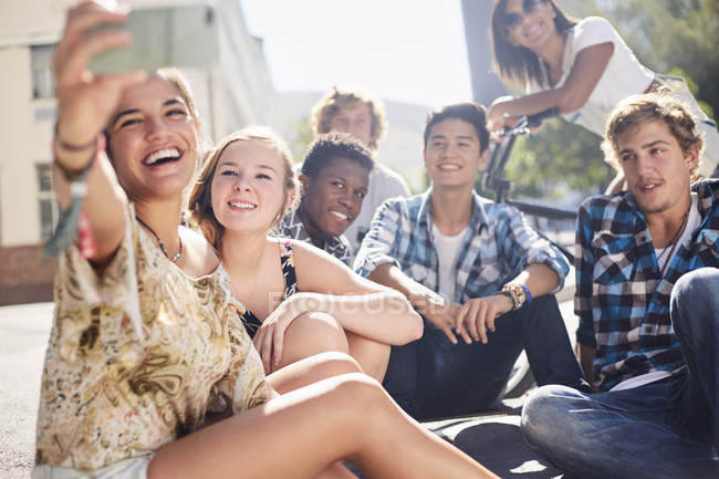 Smiling teenage friends posing for selfie on sunny urban street — Stock Photo