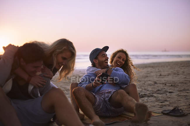 Playful couples hanging out on sunset beach — Stock Photo