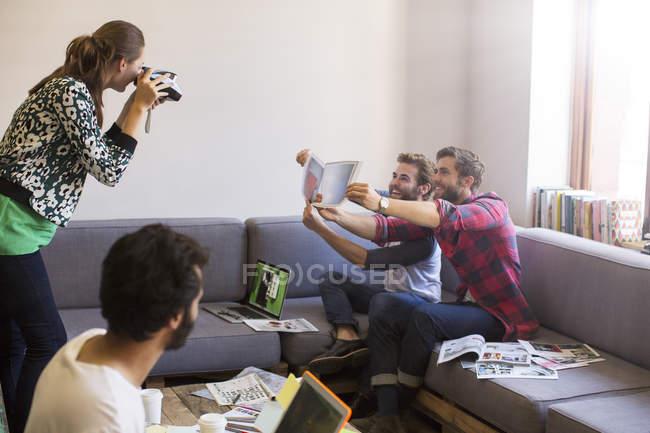 Empresarios creativos con pruebas posando para compañero de trabajo con cámara instantánea - foto de stock