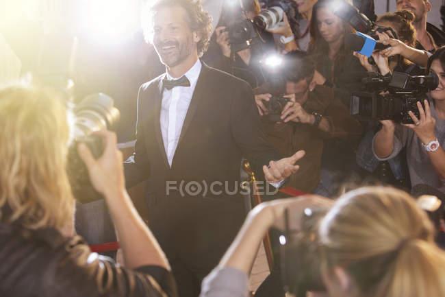 Усміхаючись знаменитості позують для фотографів папарацці на заході — стокове фото