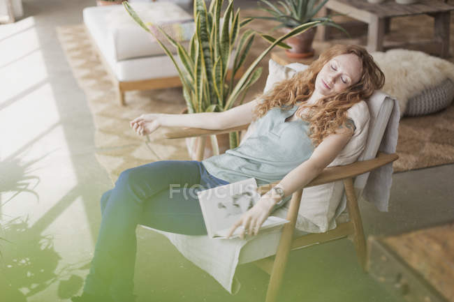 Serene woman with book napping in armchair — Stock Photo