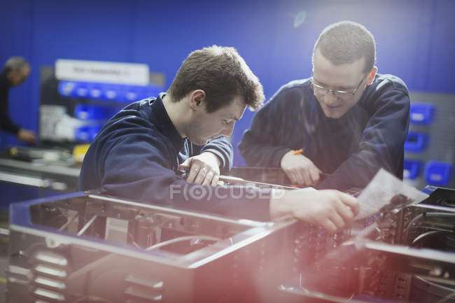 Workers inspecting machinery in steel factory — Stock Photo