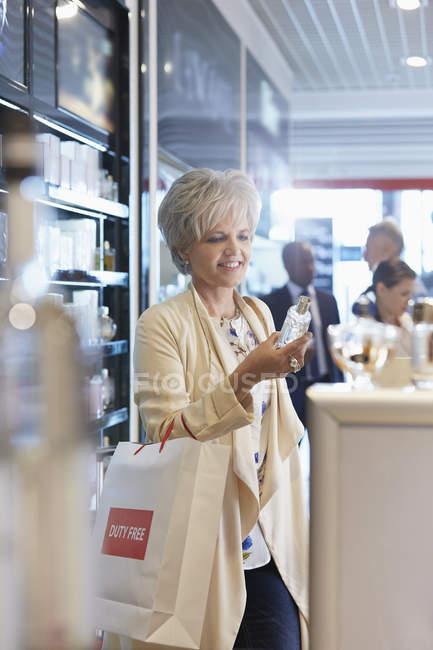 Женщина, ходить по магазинам для духов в магазин беспошлинной торговли в аэропорту — стоковое фото