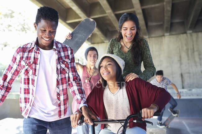 Amici adolescenti con skateboard e bicicletta BMX allo skate park — Foto stock