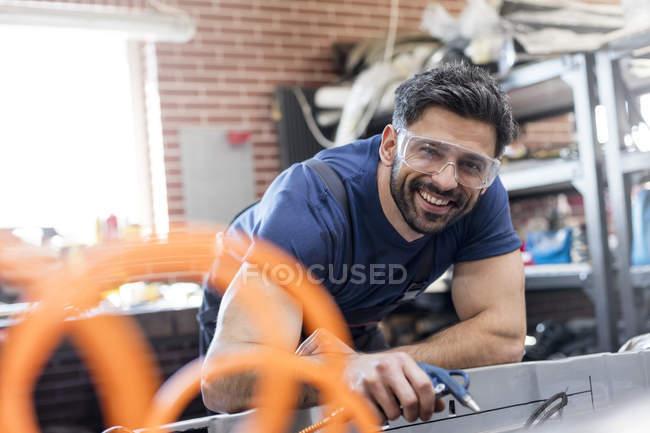 Портрет улыбающегося механика, работающего в автомастерской — стоковое фото