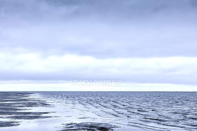 Брижі surf океану під похмуре небо — стокове фото