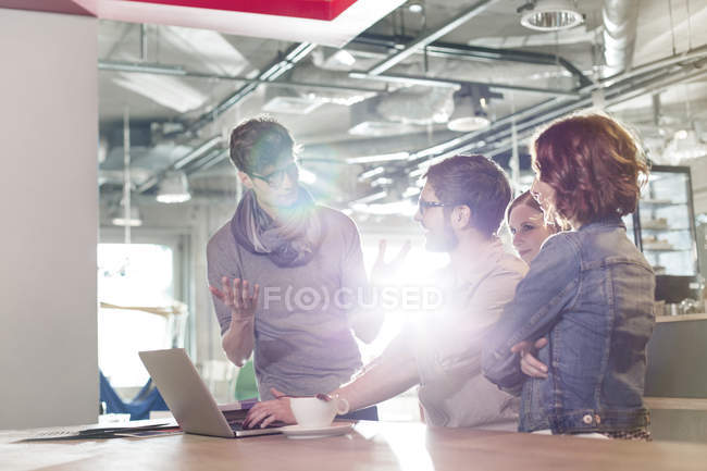 Creative business people meeting at laptop in sunny office — Stock Photo
