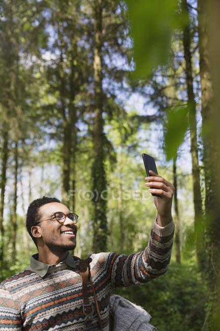 Sorrindo homem tomando selfie com câmera telefone em bosques ensolarados — Fotografia de Stock