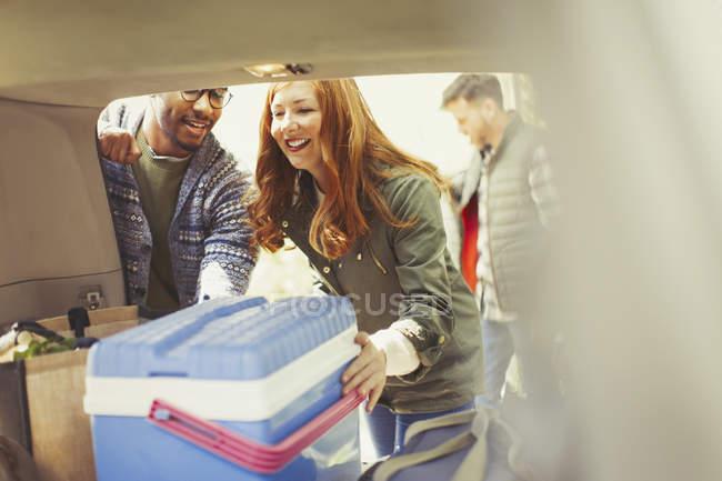 Друзья разгружают кулер с заднего сиденья машины — стоковое фото