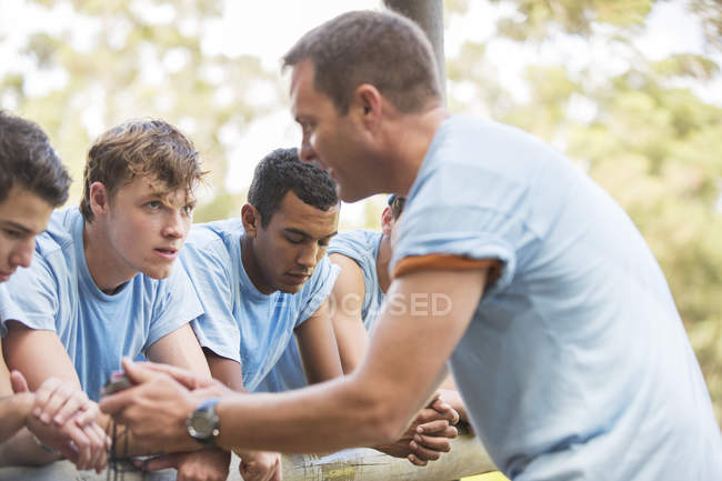 Team leader motivating tired teammates at boot camp — Stock Photo