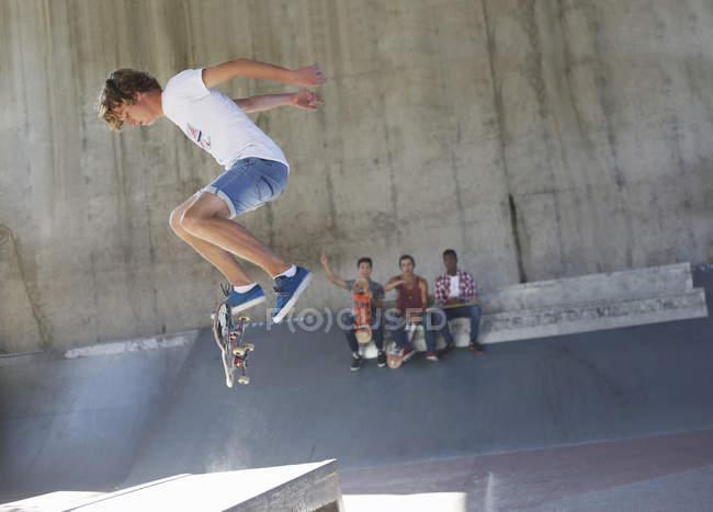 Teenage boy flipping skateboard at skate park — Stock Photo