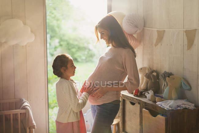 Figlia toccando lo stomaco della madre incinta nella stanza dei bambini — Foto stock
