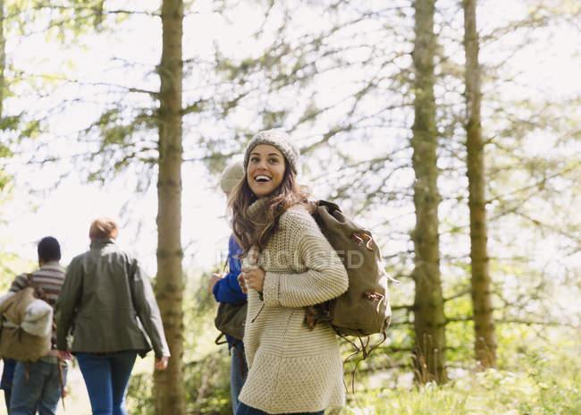Begeisterte Frau mit Rucksack Wandern im sonnigen Wald — Stockfoto