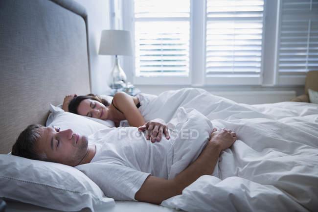 Pareja Serena durmiendo en la cama juntos - foto de stock