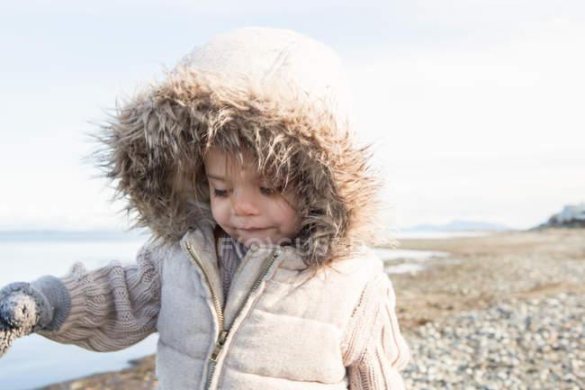 Дівчина в хутро капот куртка ходьба на пляжі — стокове фото