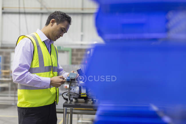 Manager examining part in steel factory — Stock Photo