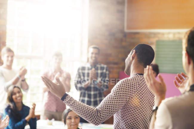 Аудиторія плескаючи для людина з руками розкритими в общинний центр — Stock Photo