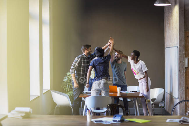 Creative business people joining hands at table in office — Stock Photo