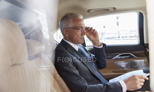 Businessman with paperwork riding in back seat of town car — Stock Photo