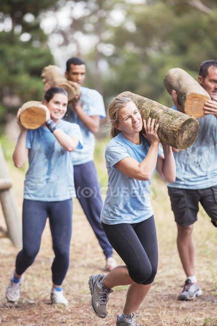 Pessoas determinadas correndo com logs no curso de obstáculos do acampamento de inicialização — Fotografia de Stock