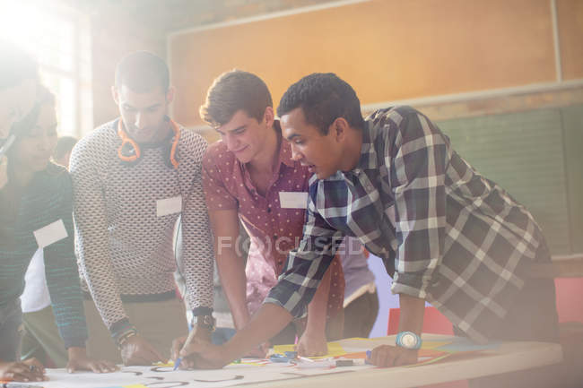 Creative business people reviewing proofs in meeting — Stock Photo