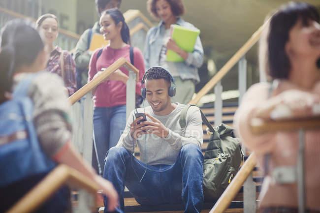 Hombre estudiante universitario escuchando reproductor de mp3 en la escalera ocupada - foto de stock