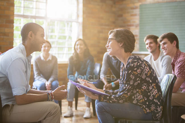 Group watching man and woman talking in group therapy session — Stock Photo