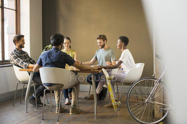 Creative business people holding hands at table in meeting — Stock Photo