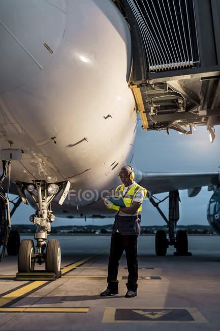 Personnel au sol de l'aéroport avec presse-papiers sous l'avion sur l'aire de trafic — Photo de stock