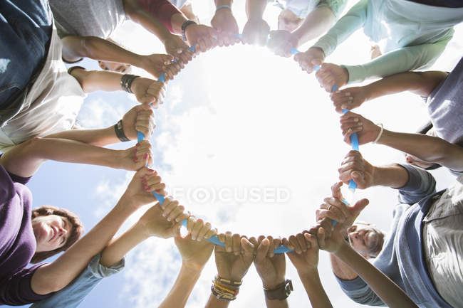 Team forming connected circle surrounding plastic hoop — Stock Photo