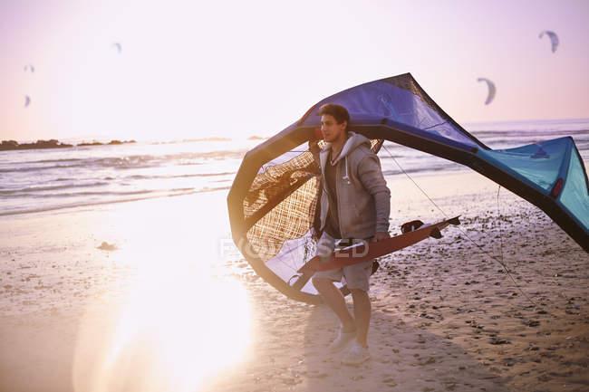 Man carrying kiteboarding equipment on sunset beach — Stock Photo
