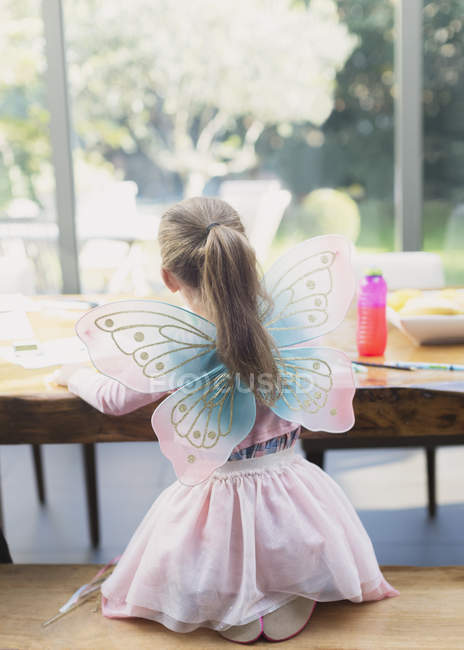 Rear view of girl in fairy wings coloring at dining table — Stock Photo