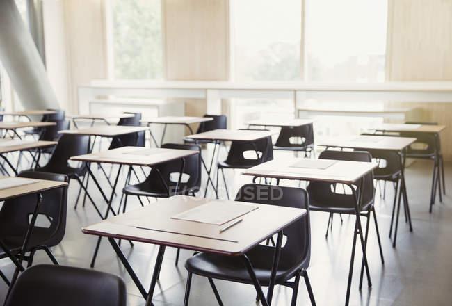 Test sulle scrivanie interno aula vuota — Foto stock