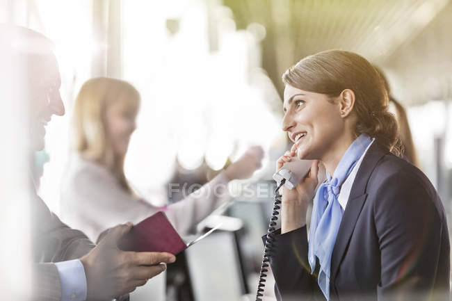 Customer service representative talking on telephone helping businessman at airport check-in counter — Stock Photo
