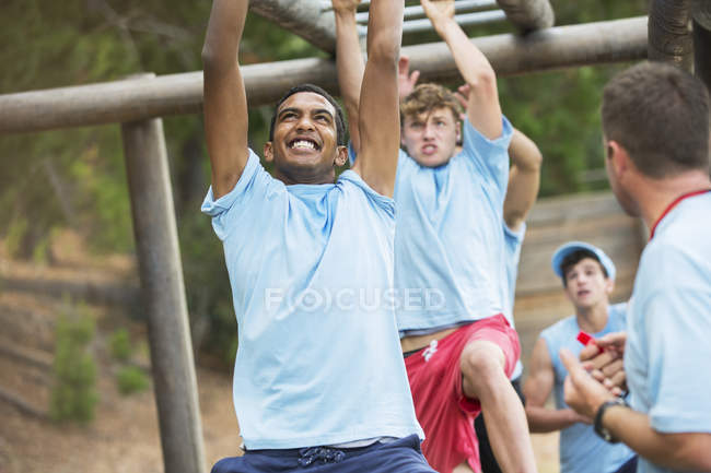 Решительные мужчины, качающиеся на обезьяньих прутьях на полосе препятствий учебного лагеря — стоковое фото