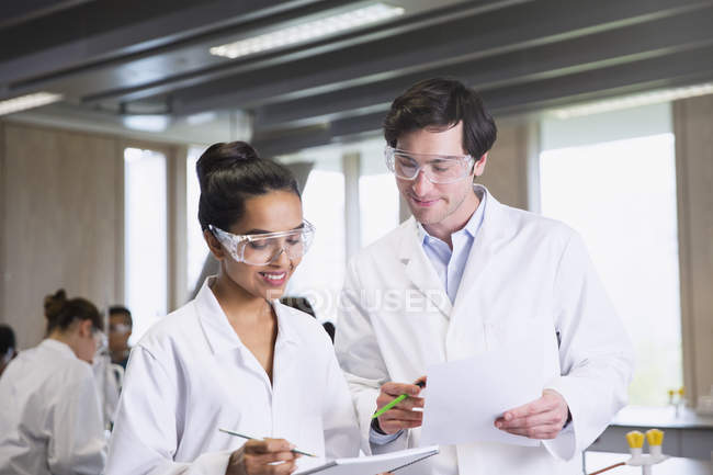 College students in lab coats discussing notes in science laboratory classroom — Stock Photo