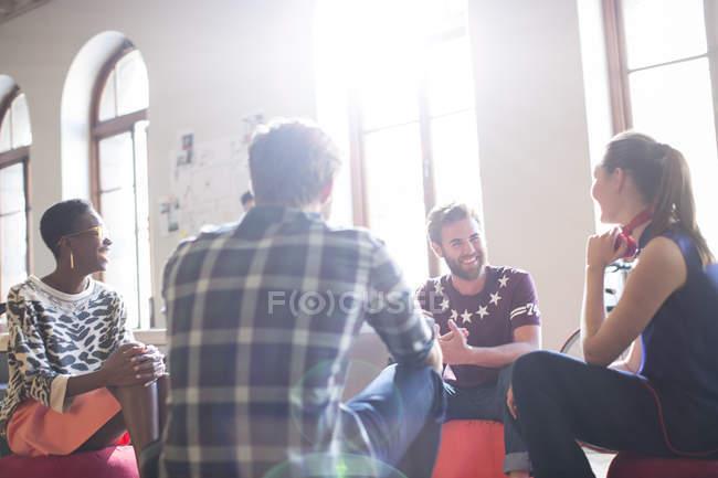 Gens d'affaires décontractée réunis en cercle au bureau ensoleillé — Photo de stock