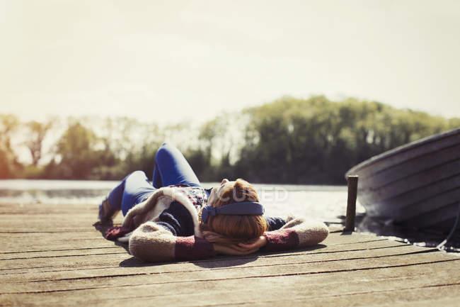 Жінка розслабляючий покладення док, слухати музику з навушниками в сонячному березі озера — стокове фото