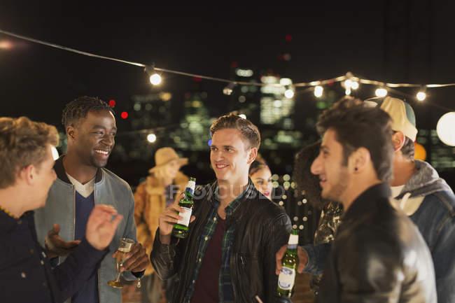Giovani uomini che bevono birra e parlano alla festa sul tetto — Foto stock