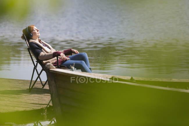 Mulher Serena relaxar ouvindo música com fones de ouvido no cais do Lago ensolarado — Fotografia de Stock