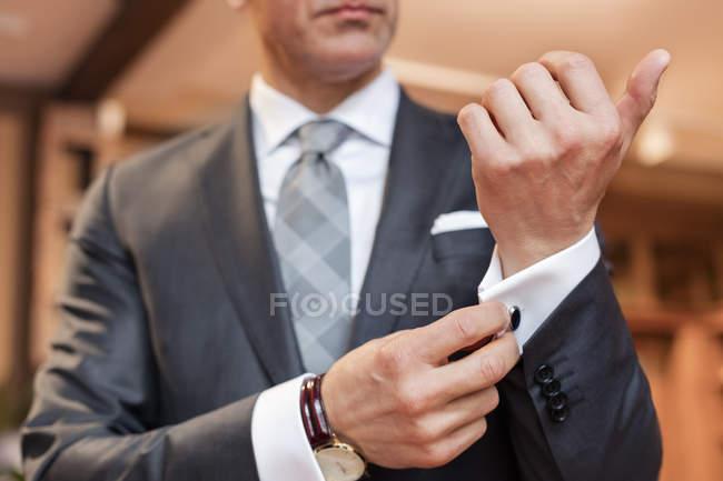 Close up well-dressed businessman adjusting cufflinks — Stock Photo