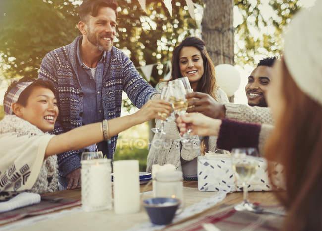 Друзья пьют бокалы для шампанского за обеденным столом — стоковое фото