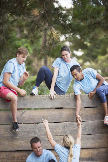 Teammates helping woman over wall on boot camp obstacle course — Stock Photo