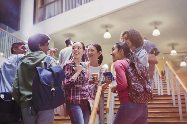 Estudiantes de la Universidad hablando juntos en escalera - foto de stock
