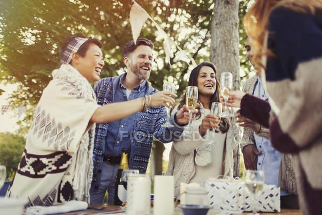 Amigos brindando taças de champanhe na mesa do pátio — Fotografia de Stock