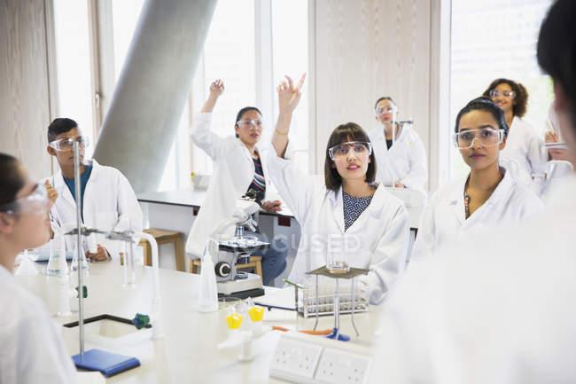 Студенты колледжа поднимают руки в классе научной лаборатории — стоковое фото