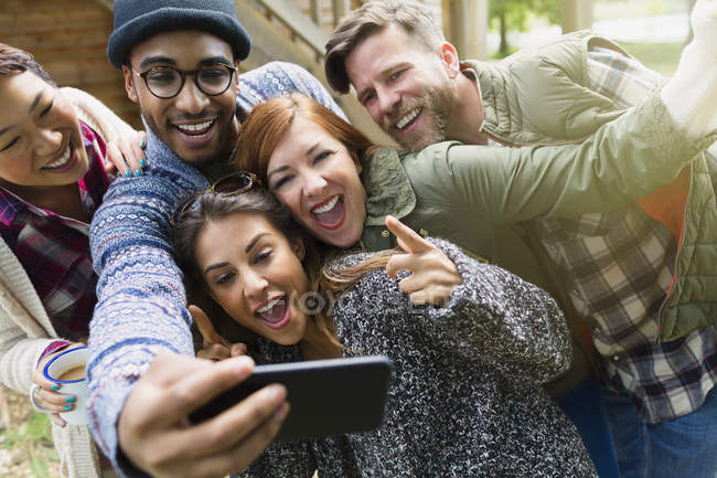 Amici allegri con fotocamera telefono cellulare gesturing prendendo selfie — Foto stock