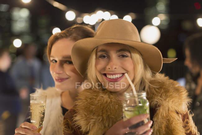 Ritratto sorridente giovani donne che bevono cocktail alla festa — Foto stock