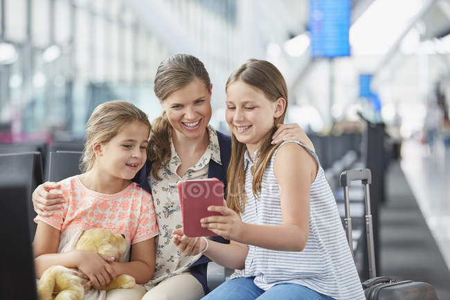 Mother and daughters using digital tablet in airport departure area — Stock Photo