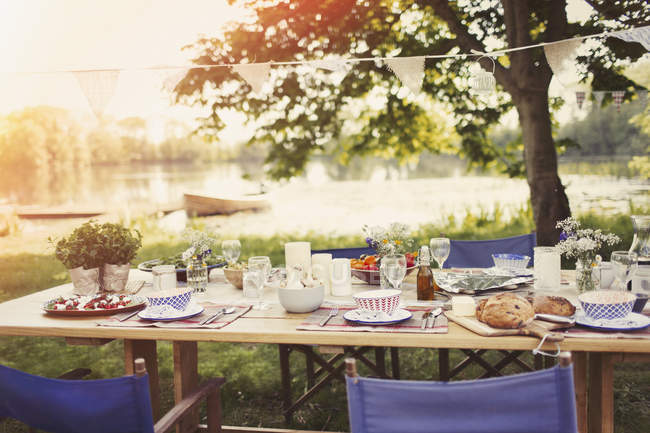 Garden party lunch on table at idyllic lakeside — Stock Photo